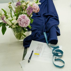 a roll of blue fabric,a tape measure drapes over it and a tech pack is seen next to it on top of a cutting table